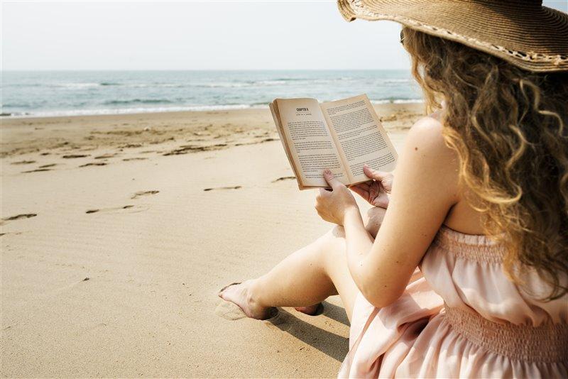 Sahilde kitap okuyan hasır şapkalı kız